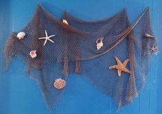 Fish net hung on blue wall decorated with seashells and starfish. Beach Theme Bathroom, Nautical Bathrooms, Beach Room, Beach Bathrooms, Baby Bathroom, Seaside Decor, Beach Wall Decor, Beach House Decor, Coastal Decor
