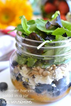 This Summer Harvest Salad in a Jar - greens with blueberries, mandrain oranges, feta cheese, almonds, sunflower seeds, and a light honey orange vinaigrette.