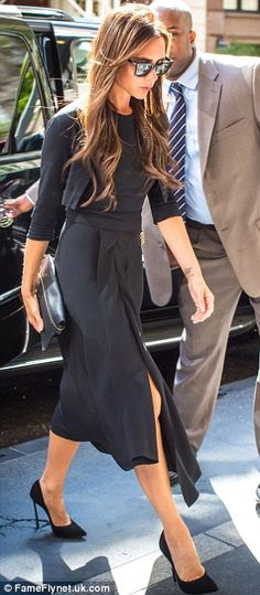 Elegant: The fashion designer VB looked stylish in a long dark blue dress and a cropped cardigan