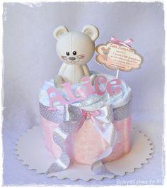 Une adorable petite souris Vulli en caoutchouc alimentaire assise sur un moelleux de couches bébé jetables pour une petite princesse prénommée Alice