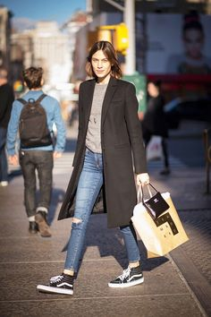 Alexa Chung wears a gray sweater, black coat, jeans, and Vans sneakers