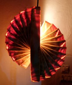 Enigmatic oval hanging lamp (Vertical) with sideview looks intriguing because of the shell-shape with warm white light inside.