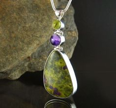 Unique handcrafted sterling silver pendant featuring Australian Gaspeite, Amethyst and a vibrant cabochon of green  Australian Serpentine with inclusions of purple Stichtite.