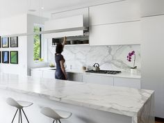 Modern white Toronto kitchen with a marble island and custom white aluminum cabinets