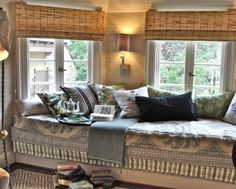 reading-nook-of-a-room-with-elegant-chapter-11-mattress-decorated-with-artistic-print-cover-and-completed-with-multiple-pillows-there-are-also-wall-lamp-and-glass-windows-500x402