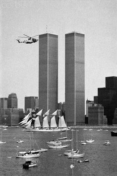 """The Twin Towers with the Schooner """"Juan Sebastian De Elcano"""" cruising by, as well as the Coast Guard in a Helicopter, in New York Harbor. Again, this looks like the Where are the color photos? World Trade Center Nyc, Trade Centre, Monuments, Photo New York, New York Architecture, New York Harbor, New York Pictures, Tall Ships, Old Photos"""