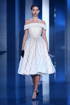 Bell silhouette. Off-white wool crêpe off-the-shoulder dress with pearl and crystal embellishment.