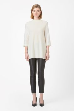 A long tunic style, this fine-knit wool jumper has contrast 3/4 sleeves in a crisp blend of silk and cotton. Designed for a loose fit, it is an A-line shape with a high ribbed neckline and metal zip fastening along the back