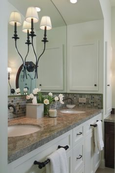 Kid's Bathroom. Love the tile work, the towel bars on the cabinet fronts, the idea of a light fixture mounted in the middle of the mirror...