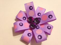 Purple hair bow with button center on a clip