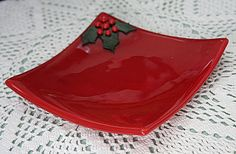 This red Christmas plate has aventurine green holly leaves and red berries fused to the surface. It measure 6 3/4 square. It has been through
