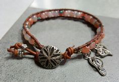 Soft coral Mountain Jade beads stitched onto brown leather. Silver Sand Dollar button closure. Accented with a cute flip flop and filigree heart charms