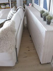 behind the couch in front of window... great ledge for drinks instead of end tables With wheels! Easy to sweep under.
