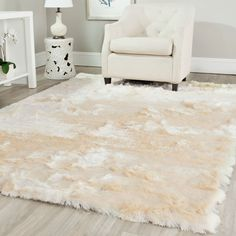 Add a touch of lavish, contemporary style to any indoor living space with this hand-woven ivory and tan shag rug. Handmade from durable polyester for easy cleaning and maintenance. It has a deep, shaggy pile with a silky texture for maximum comfort.