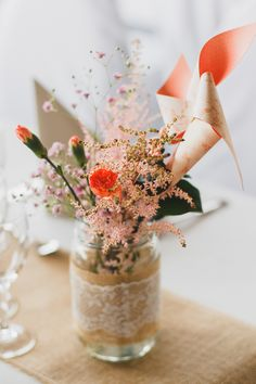 Sweet wedding centerpiece idea alert! Mason jars wrapped with burlap and lace filled with flowers plus paper windmills for a dash of whimsy! | Marine Szczepaniak Photography
