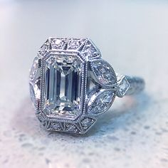 Vintage styling floral emerald cut halo engagement ring