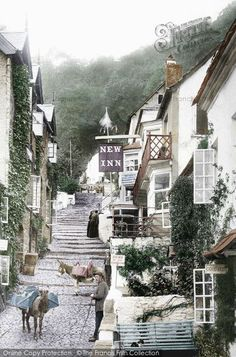 Clovelly, Main Street 1894 Clovelly hangs on the side of the hill, fringed by luxuriant woodland.  The New Inn is still there, offering rest and refreshment to visitors. Unlike most villages, the whole area is owned by a Trust, who charge visitors a fee.