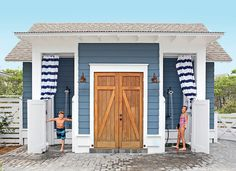 Blue outdoor shower with saloon-style swinging doors, striped shower curtains, and handsome sconces.