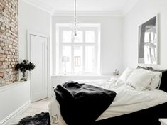 Clean white room with exposed brick wall and clear bubble lighting