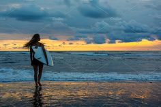 Female surfer with board in hands walking along coastline on sandy beach over sunset by olsin on @creativemarket