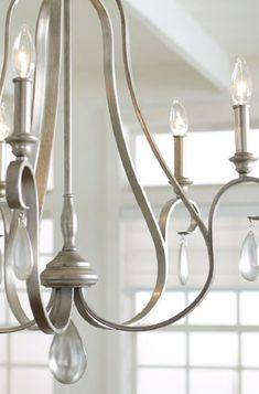 This lustrous Chandelier is reminiscent of provincial France displaying romantic curved lines, candle-like light sleeves and stunning teardrop detail. The traditional design has been amplified with a modern Sunrise Silver finish to amplify the elegant silhouette. Make a spectacle of this stunning Chandelier in your living room, above your dining table or in your foyer. Shop Lighting Collective >