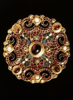 The Fibula Dorestad: One of the most famous archaeological finds from the Netherlands, found in 1969 in a well in Dorestad. The gold brooch is inlaid with different colors of glass, almandine (red gemstone) and pearls along the edge. The style is that of ecclesiastical silverware Burgundian workshops from the time of Charlemagne. c. 775-800 AD. Rijksmuseum van Oudheden.