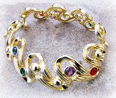 Elegant Bracelet, Vibrant Jewel Toned Faceted Stones in Ruby Red, Sapphire Blue, Emerald Green and Amethyst Purple. Contemporary yet classic style. Crystals are open backed and bezel set scattered along ribbon style links. Fold over Clasp. Marked with stamped Swarovski Swan Logo. 7 inch length See my entire shop here: https://www.etsy.com/shop/SentimentalVintager