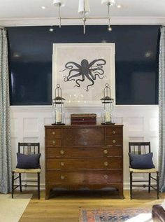 Foyer w/ Two chairs flanking an Antique Chest, paneled white walls w/ chair railing.  .Love the navy lacquer. Modern light fixture. Modern Octopus Art in Navy/White.
