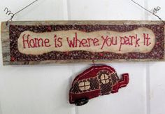 One of my favorite things to do is to grab some fire wood, a few blankets, and my daddys pop-up camper, and head to the Smoky Mountains...or anywhere in Gods country...for a dose of sweet non-city air. Im willing to bet I aint alone.  So I took some deep red thread, and hand-stitched (freehand) onto repurposed linen, Home is where you park it The linen is backed with some upcycled floral cloth (brown with lavender, red, and white flowers...)  Hanging from the sign is a little burgundy…