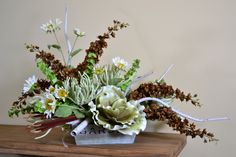 I love the garden feel of this arrangement with the white birch branches, fantasy succulent, white sunflowers, and bronze delphinium from Trees n Trends