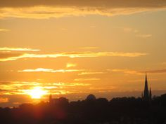 Anthony J Sargeant took this photograph from his Hotel bedroom window.  Flamsteed House with its signal ball is just to the right of the sun and further  to the right is the dome of the Royal Observatory in Greenwich Park