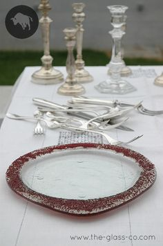Elegant table setting with handcrafted dinnerware designed by Glass Studio. The dinner plate is in transparent glass decorated with red glass beads on the rim.
