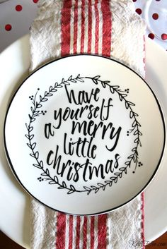Love these graphic black and white Christmas plates with a different saying on each and red striped napkins from HomeGoods on this festive tablesetting! kellyelko.com sponsored pin