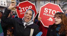 Concentración de la Plataforma de Afectados por las Hipotecas con carteles de Stop Desahucios en una sucursal de Bankia, en Alicante.