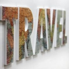 spell out TRAVEL with maps glued onto wood letters