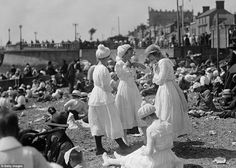 Bathing belles show off the modest white cotton calf length long sleeved dresses, complete with bathing caps adorned with bobbles, on the beach at Southend-on-Sea, Essex in August 1919 | beachwear from a century ago