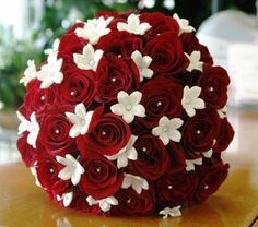 I think the red accent would look GREAT with the blue, silver and white. Red roses with jewels and white stephanotis for TJ and the bridemaids could carry small white rose bouquets.