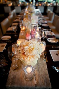 Table Decor - flowers and candles on wooden plank. Dark table cloth.