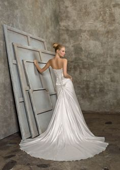 A slight flare of this fitted gown flows to the hem and creates a marvelous look for the chapel train. Grace and style show through as the lovely corset back cinches the bodice and highlights the ruching over the derriere. If you feel like a goddess when you slip on this satin creation, you are feeling the promise the gown makes for your wedding day! #timelesstreasure