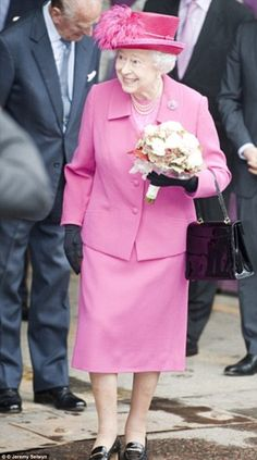 The Queen wore a bright pink outfit with a black patent Traviata bag to attend the 50th anniversary of the National Theatre in 2013