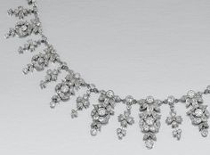 [Detail]   DIAMOND NECKLACE, EARLY 20TH CENTURY.  Designed as an articulated fringe of graduated floral and foliate motifs millegrain-set with circular-cut diamonds to a back chain of knife-edge links collet -set with similarly cut stones, length approximately 430mm, one small diamond deficient