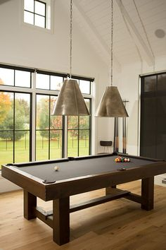 Game Room Lighting. Game room features a paneled cathedral ceiling lined with two Goodman Hanging Lamps suspended over a pool table. #GameRoom #Lighting #GoodmanHangingLamps Hahn Builders.