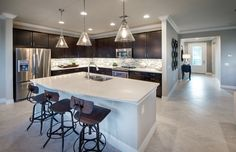 This bright kitchen is accented perfectly by dark cabinets and sleek fixtures. | Pulte Homes