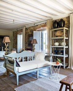 large rustic Finnish living room, painted wood bench, wide old floorboards, stone walls
