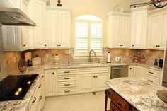 Cream Cabinets with Bronze Hardware, Granite Stone Countertops, and Undermount sink and faucet with foot pedal control