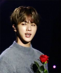 Jin smiling with rose gif