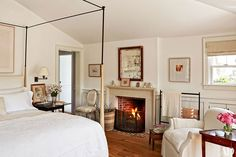 A master bedroom is anchored by a Rose Tarlow Melrose House four-poster; the Portland limestone mantel is by Chesney's.