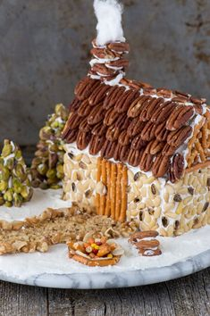 A rustic christmas gingerbread house made using nuts! Learn how to make a gingerbread house out of a butter box, plus tons of decorating ideas and the best gingerbread 'glue'! Gingerbread House Pictures, Gingerbread House Designs, Gingerbread House Parties, Christmas Gingerbread House, Gingerbread Houses, Rustic Christmas, Gingerbread Recipes, Christmas Appetizers, Christmas Desserts