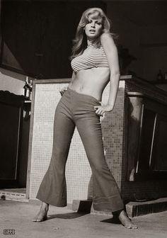 """Rachel Welch veste calça Saint-tropez na década de 70. Calça popular na década de 60 e 70, com a cintura extremamente baixa. A calça ganhou o nome da cidade situada no litoral francês, a Côte D'Azur, na costa mediterrânea, entre Nice e Marselha. O pequeno vilarejo de pescadores ganhou notoriedade quando Brigitte Bardot foi morar lá nos anos 1960, e usava calças de cintura baixa e bocas largas. """"As calças bocas de sino estiveram para os anos 70 tanto quanto os vestidos merengue para os 50."""