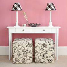 Skinny wood base lamps with black and white plaid shades. Pink, white and black. Cute printed ottoman cubes.
